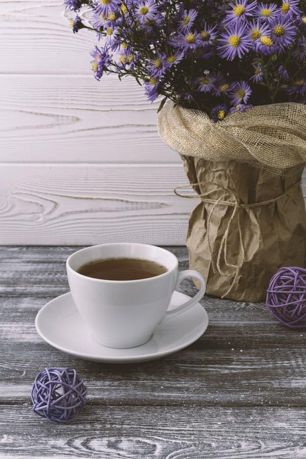 Romantisk bakgrund med en kopp te, lila blommar i en vas på en grå trätabell royaltyfri foto