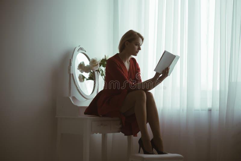 Romantisk berättelse den eleganta kvinnan läste romantisk berättelse bok med romantisk berättelse romantisk berättelseläsning fan royaltyfria bilder