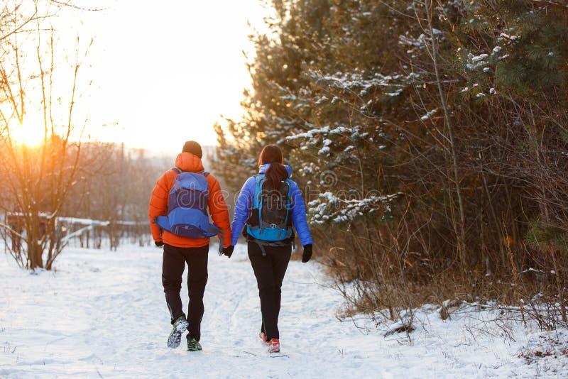 Romantisk bild från baksida av mannen och kvinnan med ryggsäckar i vinter royaltyfria bilder