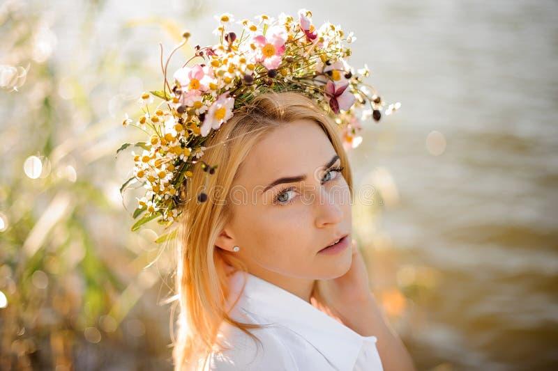 Romantisk blond flicka i en krans av blommor royaltyfri foto