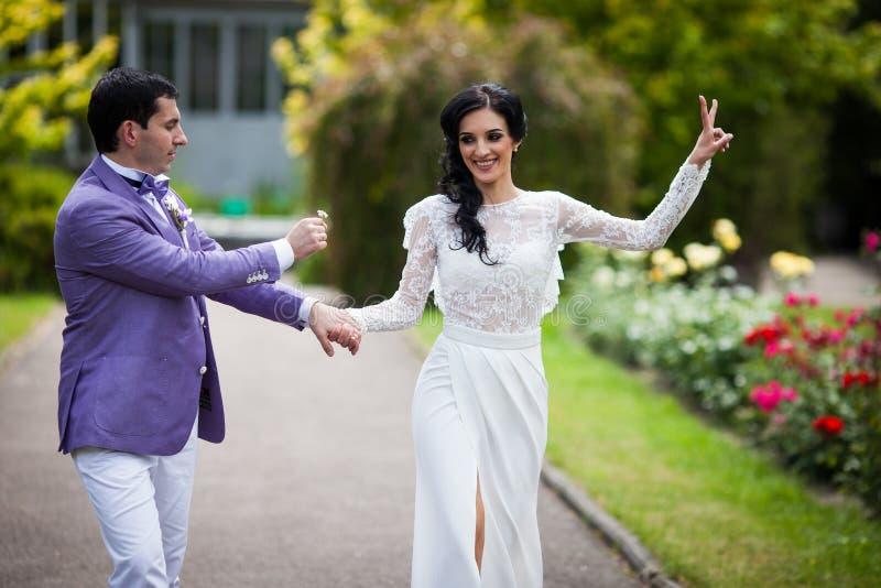 Romantisk brudgum i gifting blomma för liladräkt till den härliga bruden royaltyfri fotografi
