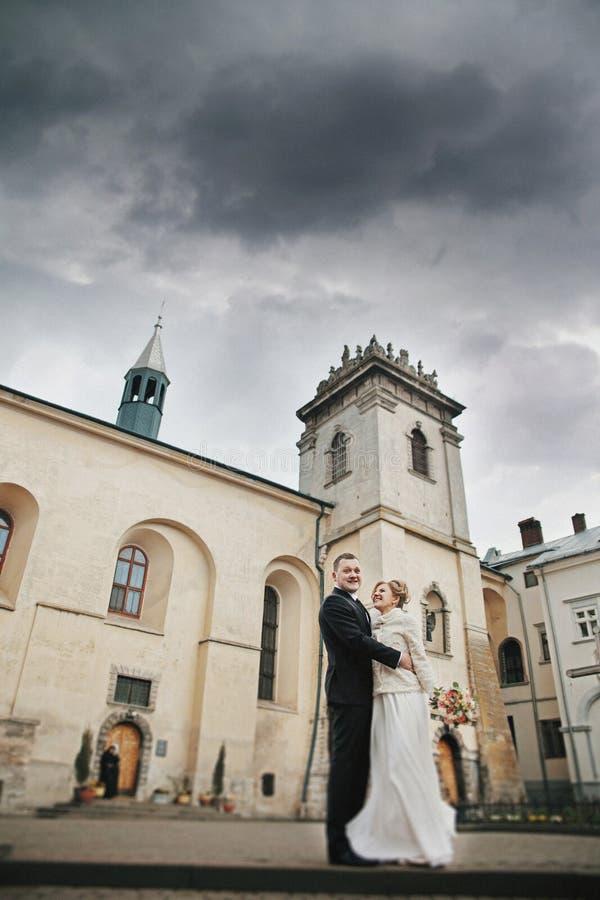Romantisk brudgum som kramar den härliga bruden nära gammal kyrka med towe royaltyfria foton
