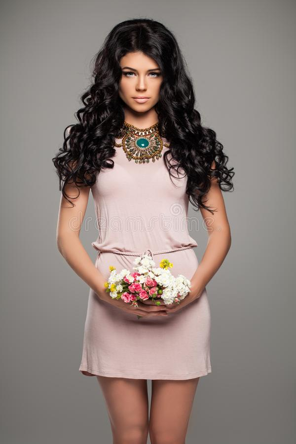 Romantisk brunettkvinna i rosa sommarklänning royaltyfria foton