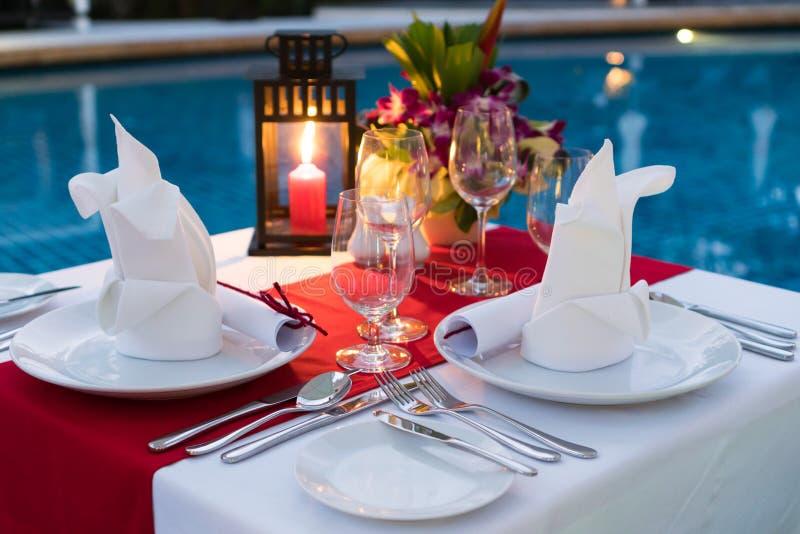 Romantisk Candlelit matställetabell; Poolside med tabelluppsättningen arkivfoto