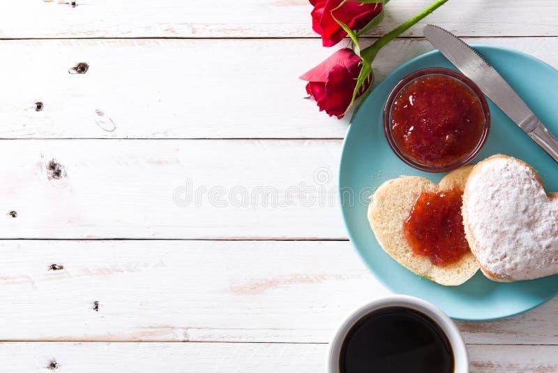 Romantisk frukost med denformade bullen, kaffe, bärdriftstopp och rosor royaltyfri foto