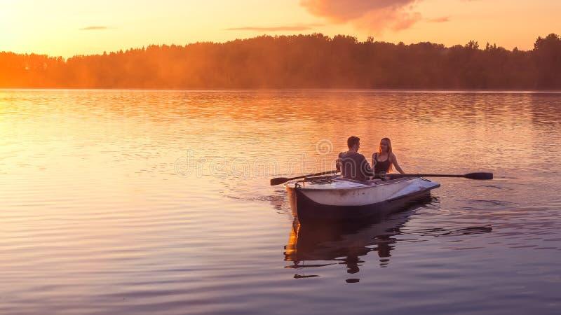 Romantisk guld- dimma för solnedgångflodsjön som älskar för litet härliga vänner ekadatum för par, rider under lycklig kvinnaman  royaltyfri foto