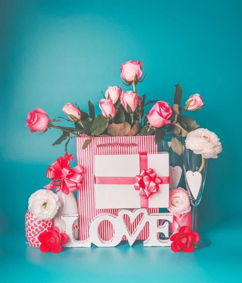 Romantisk hälsninginställning med ordet FÖRÄLSKELSE, gåvaask, hjärta, grupp av rosa blek vit flaska för rosor av champagne och ex fotografering för bildbyråer