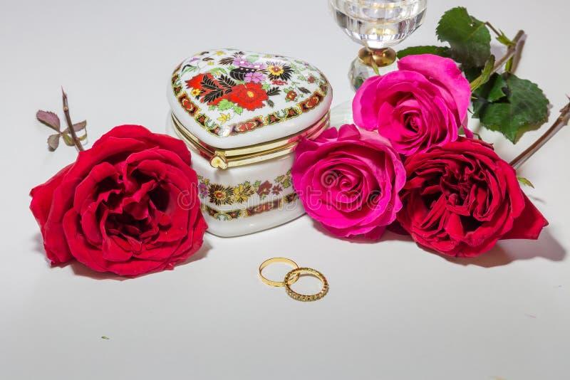 Romantisk hjärta formade den konstnärliga smyckenasken med ljusa röda och rosa rosor med guld- förlovningsringar på ljus bakgrund fotografering för bildbyråer