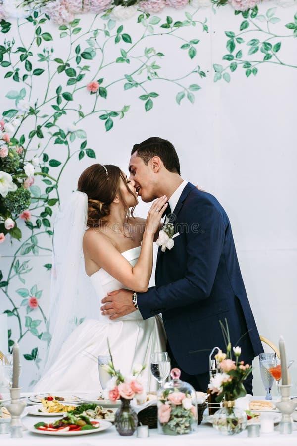 Romantisk kyss av gifta paret bredvid tabellen royaltyfria bilder