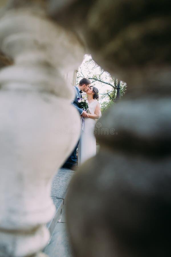 Romantisk kyss av nygift personpar Skott från den åldriga stenbalustraden royaltyfria bilder