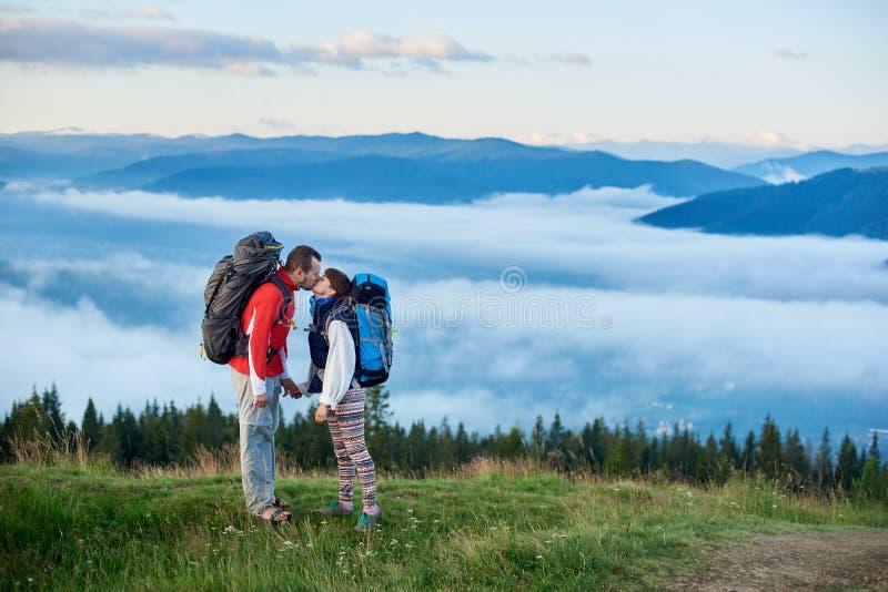 Romantisk kyss på bakgrund av väldiga berg i dimma under himmel med moln arkivbild