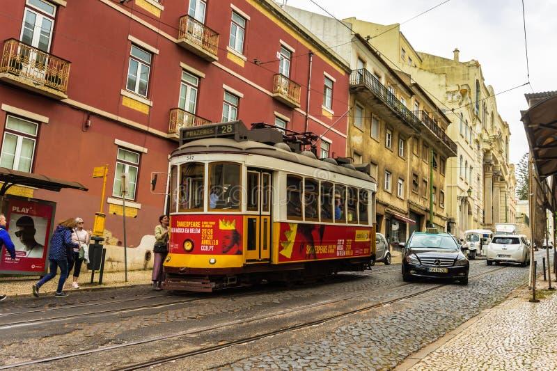 Romantisk Lissabon gata med den typiska gula spårvagnen, Portugal royaltyfri bild