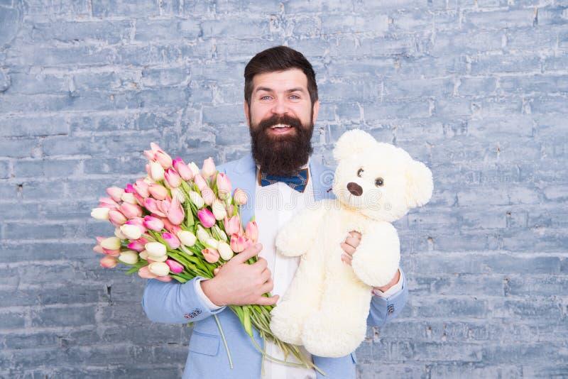 Romantisk man Macho fående klart romantiskt datum Väntande på älskling För klädersmoking för man väl ansade blommor för håll för  royaltyfria bilder