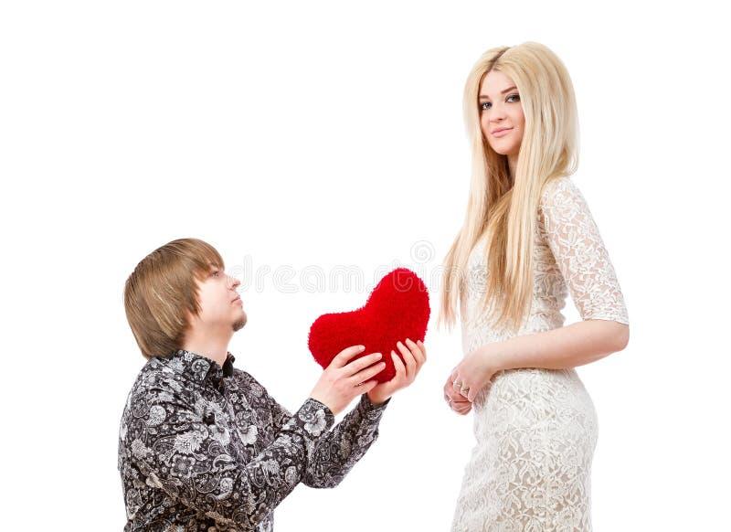 Romantisk man på hans knä som rymmer en röd hjärta och en upphetsad blo royaltyfria bilder