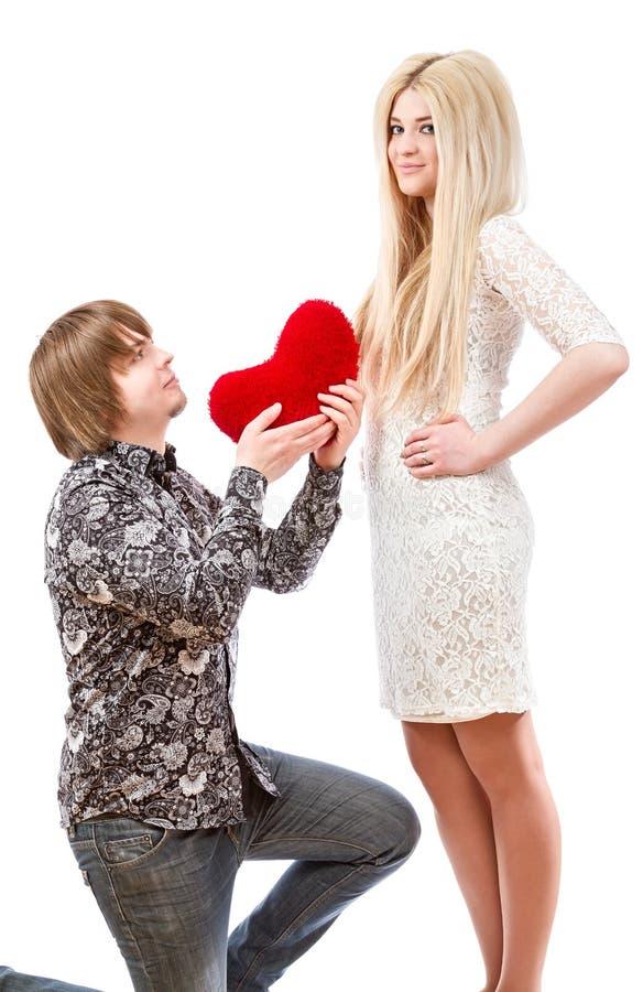 Romantisk man på hans knä som rymmer en röd hjärta och en upphetsad blo arkivbild