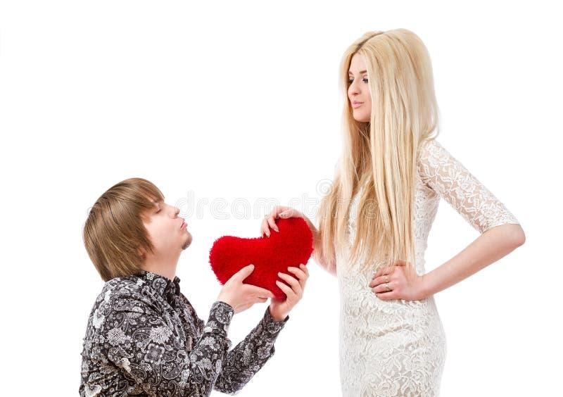 Romantisk man på hans knä som rymmer en röd hjärta och en upphetsad blo arkivfoto