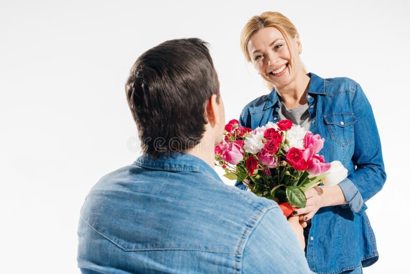 Romantisk man som ger hans flickvän en bukett av blommor arkivfoto