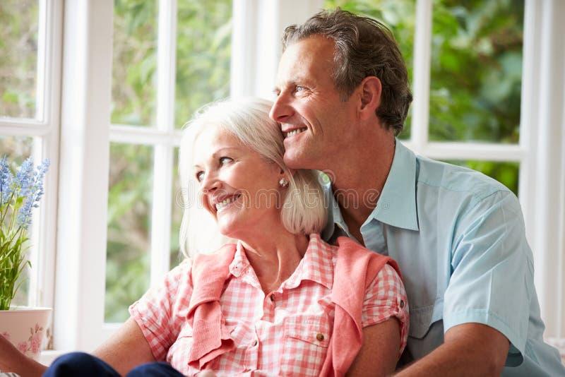 Romantisk mitt åldrades par som ser ut ur fönster arkivfoto