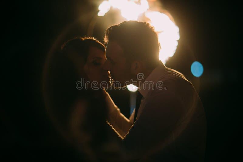 Romantisk och emotionell kyss av främst flammande hjärta för nygift personpar Nattskott med lensesignalljuset arkivbild
