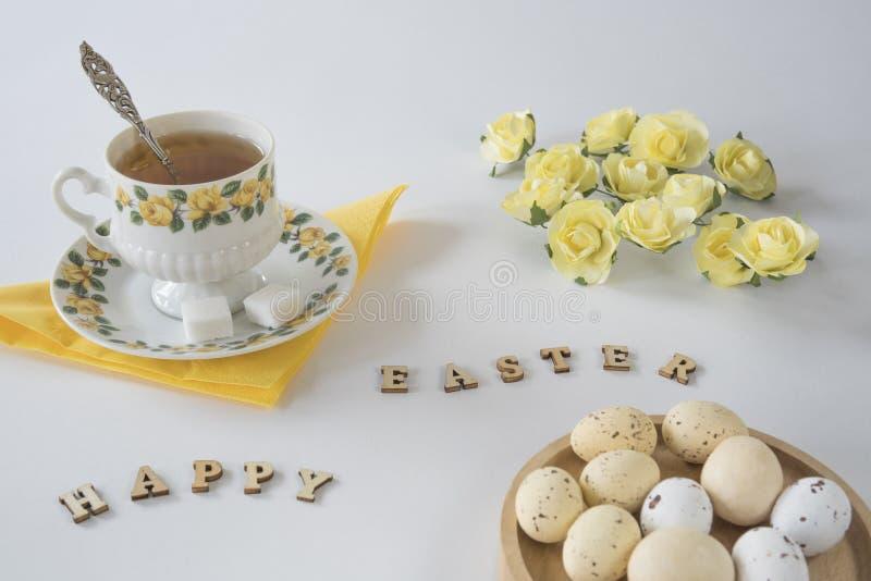 Romantisk påskplats med ägg, träbokstäver och gula rosor, på den vita tabellen arkivbild