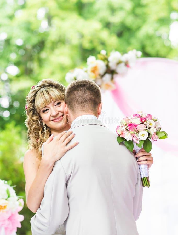 Romantisk pardans för lycklig nygift person på bröllopgången med rosa garneringar och blommor arkivfoto