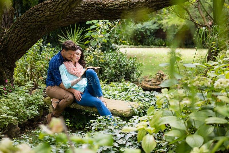 Romantisk parläsebok på bänk i trädgård arkivfoton