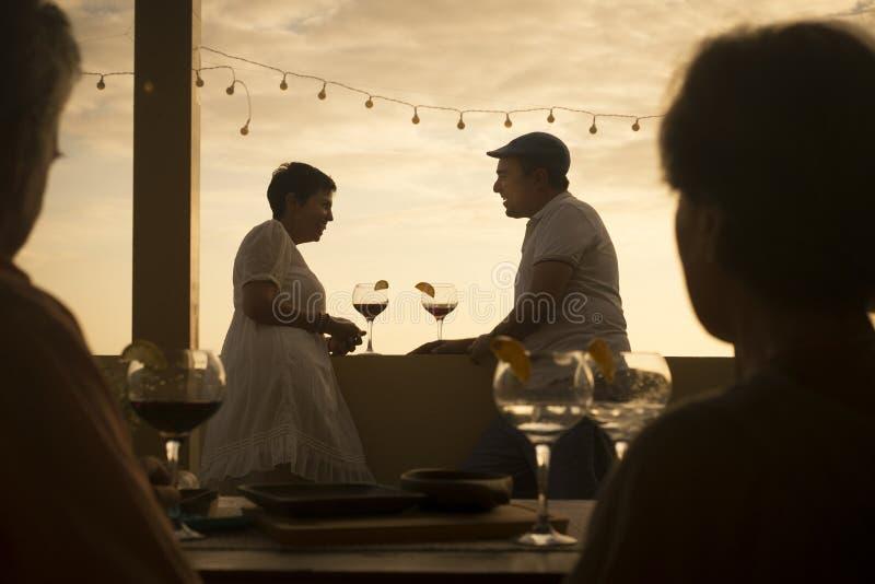 Romantisk plats med par av cacuasian mellersta ?lderfolk som tillsammans dricker en coctail i f?rh?llande under en f?rgrik guld royaltyfri fotografi