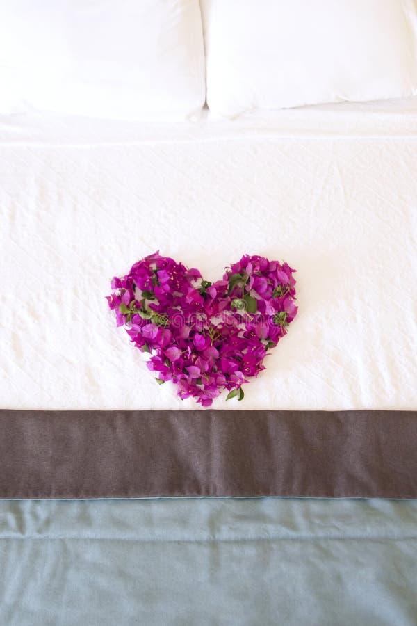 Romantisk säng med blommor arkivbilder