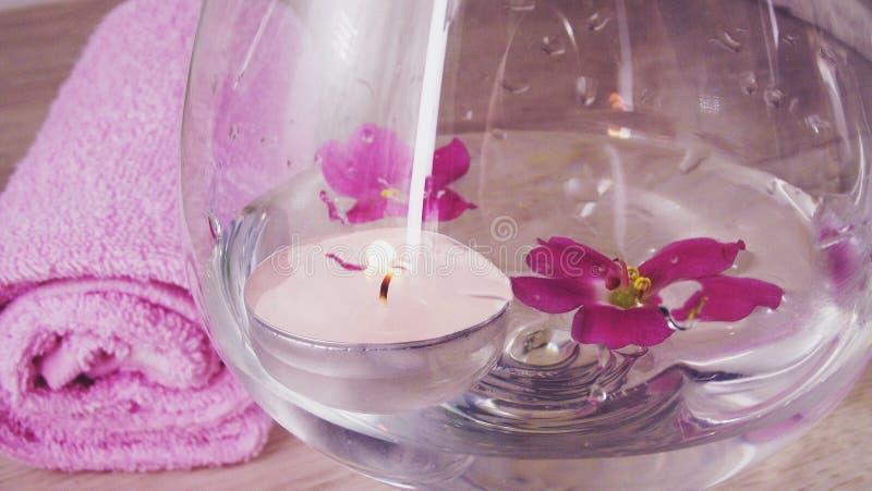 Romantisk sammansättning med en stearinljus och en violet blommar att sväva i en bunke av vatten royaltyfri foto