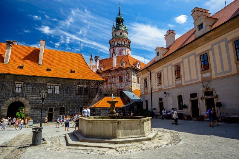 Romantisk sikt av den slotttornet och springbrunnen i borggården i Cesky Krumlov royaltyfria foton