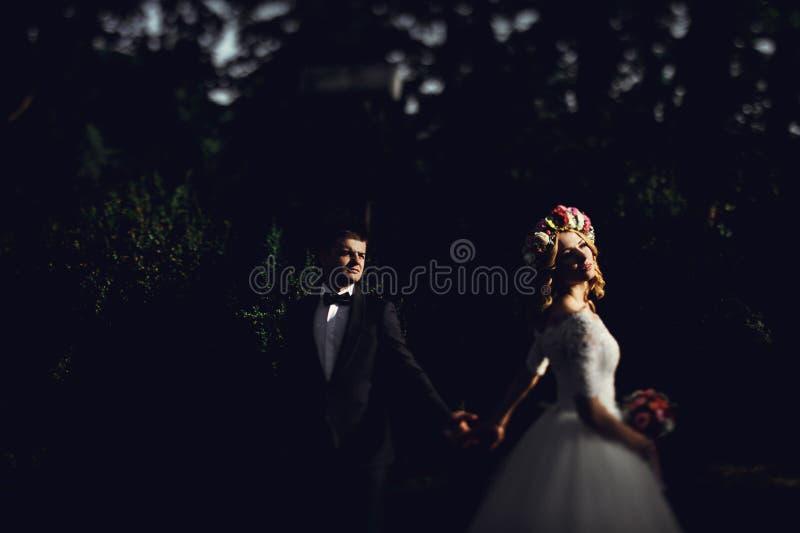Romantisk stilig brudgum i dräktinnehavhänder med ursnygg youn royaltyfria bilder
