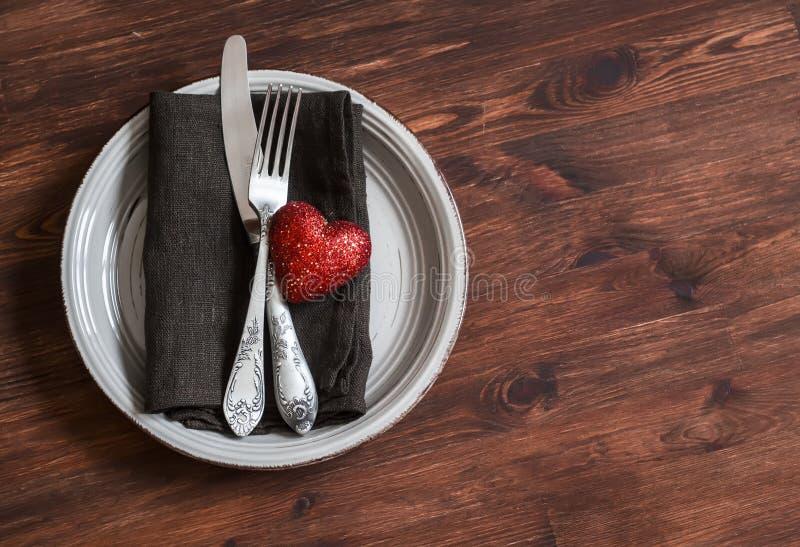 Romantisk tabellinställning - platta, kniv, gaffel, servett och en röd hjärta, för valentindag på en mörk trätabell royaltyfri foto