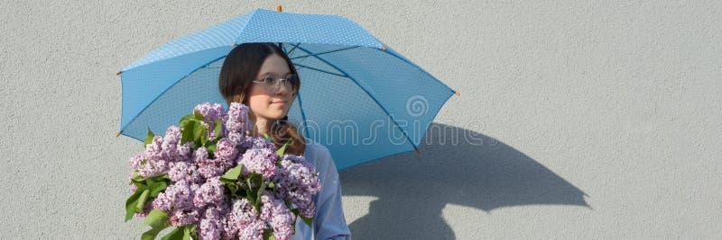 Romantisk tonårs- flicka för profilstående med buketten av lilor, med paraplyet på grå väggbakgrund Utomhus- kopieringsutrymme, arkivfoton