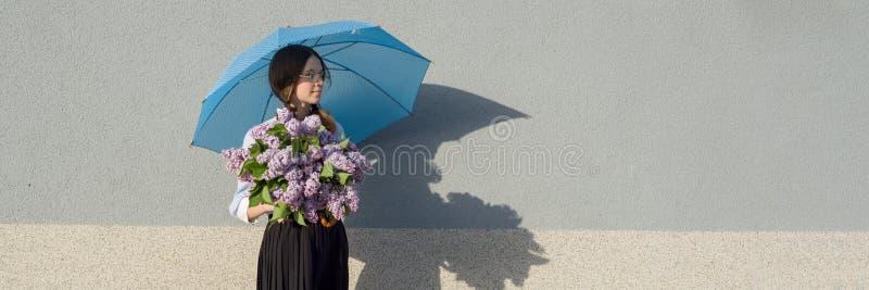 Romantisk tonårs- flicka för profilstående med buketten av lilor, med paraplyet på grå väggbakgrund Utomhus- kopieringsutrymme, arkivbild