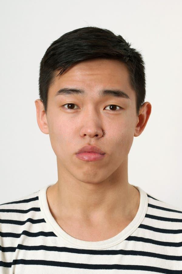 Romantisk ung asiatisk man som ser kameran fotografering för bildbyråer