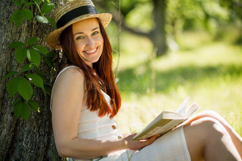 Romantisk ung dam i sugrörhatt som läser ett boksammanträde i trädgård royaltyfria foton
