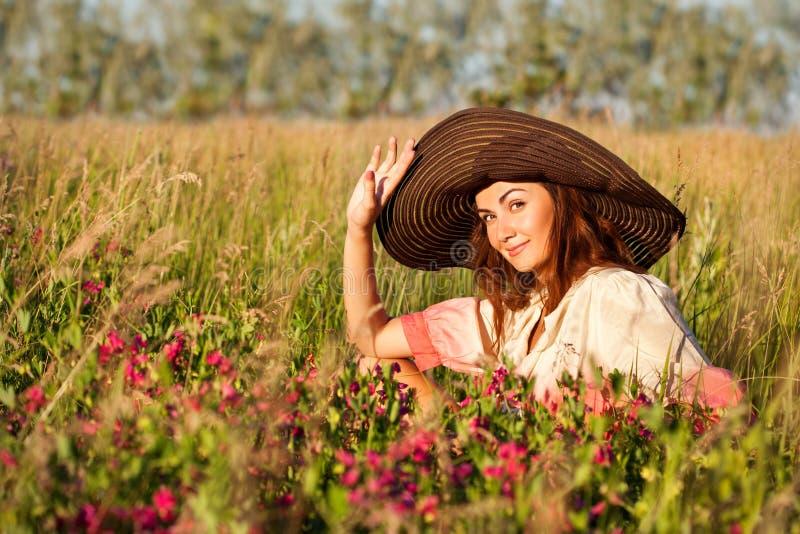 Romantisk ung kvinna i hattanseende på äng i varm sommardag royaltyfri foto