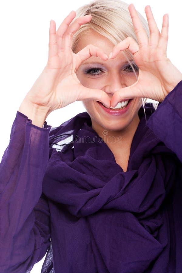 Romantisk ung kvinna som gör en hjärta att göra en gest arkivbild
