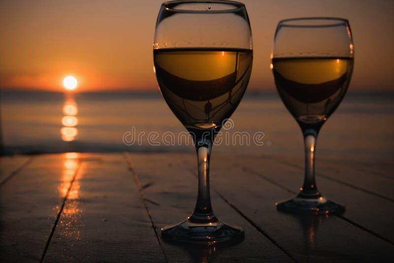 Romantisk utomhus- aktivitet Två exponeringsglas med vitt vin i en utomhus- restaurang med solnedgånghavssikten, avkopplingbegrep royaltyfria bilder