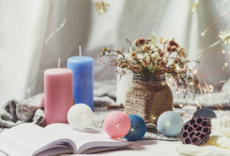 Romantisk vinter och nytt års inre sikt för stil med en stearinljus, en bok, en girland och färgade blommor i lantlig vas arkivbild