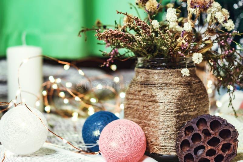 Romantisk vinter och nytt års inre sikt för stil med en stearinljus, en bok, en girland och färgade blommor i lantlig vas royaltyfri foto