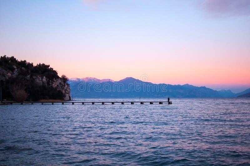 Romantisk violett solnedgång på en sjö med en wal långt pir och folk royaltyfri foto