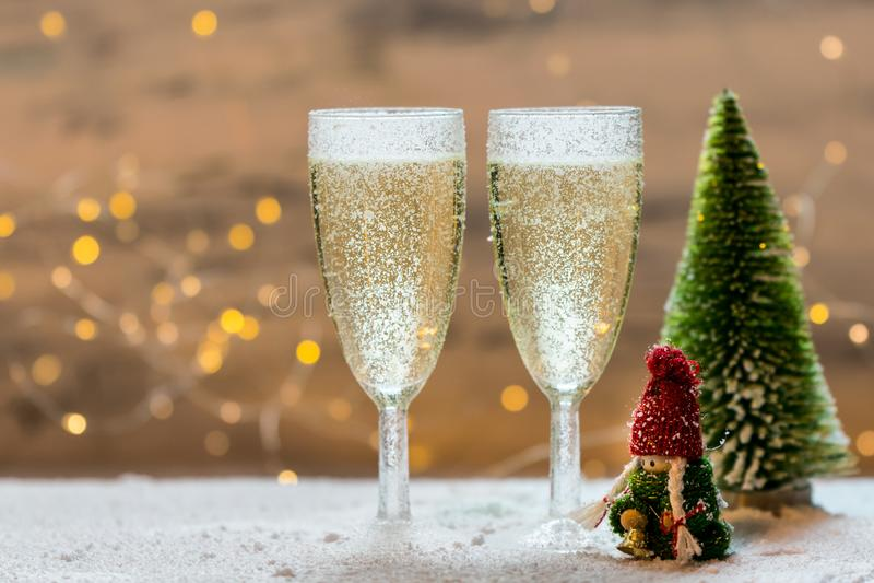 Romantisk, vit och guld- vinterbakgrund med två exponeringsglas av champagne royaltyfria foton