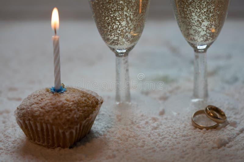 Romantisk, vit och guld- vinterbakgrund med två exponeringsglas av champagne och vigselringar fotografering för bildbyråer