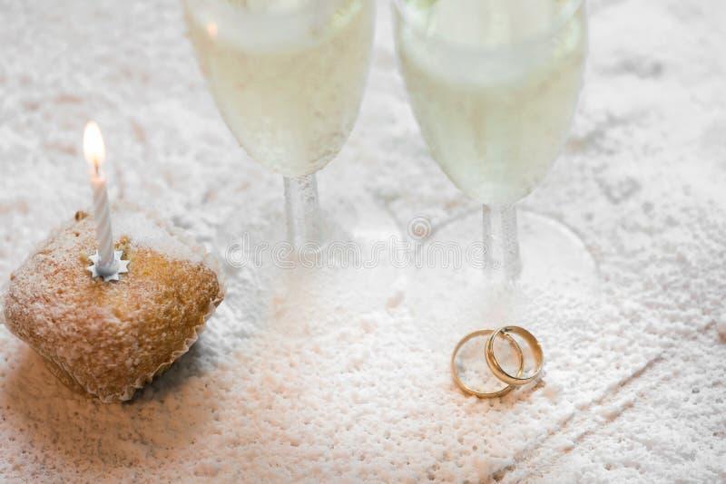 Romantisk, vit och guld- vinterbakgrund med två exponeringsglas av champagne och vigselringar royaltyfri bild