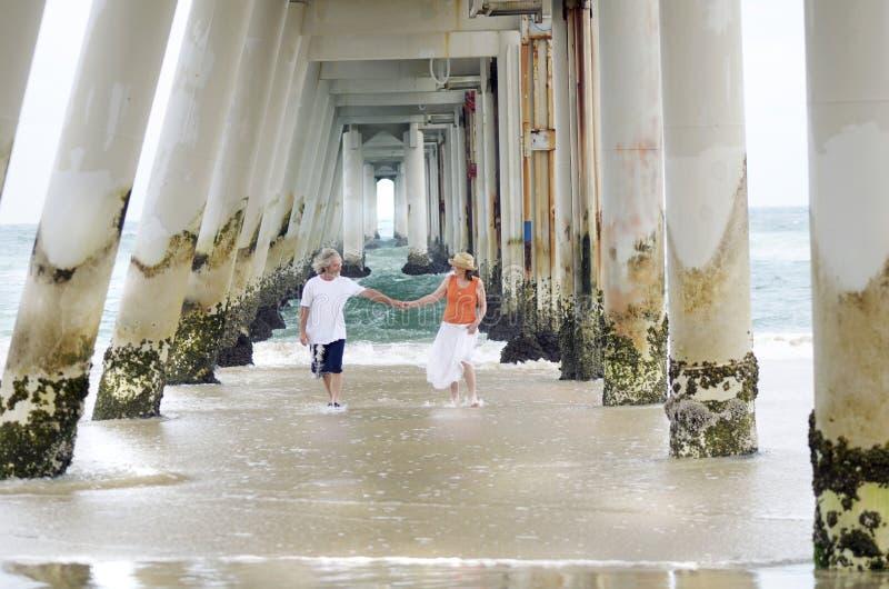 Romantiska äldre mogna man- & kvinnapar som är bekymmerslösa på strandsommartid arkivbild