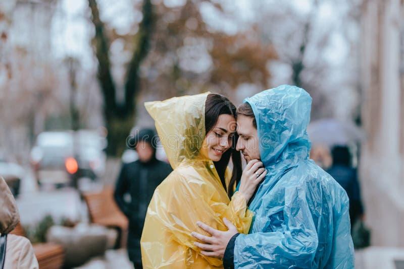Romantiska älska par, grabben och hans flickvän i regnrockarna står framsidan - - för att vända mot på gatan i regnet royaltyfria bilder