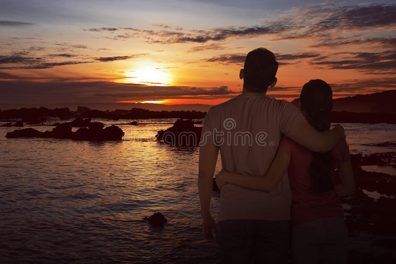 Romantiska asiatiska par som tycker om härlig solnedgång arkivbild