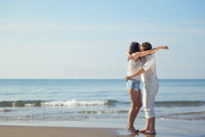 Romantiska barnpar på kyssa för strand arkivbild