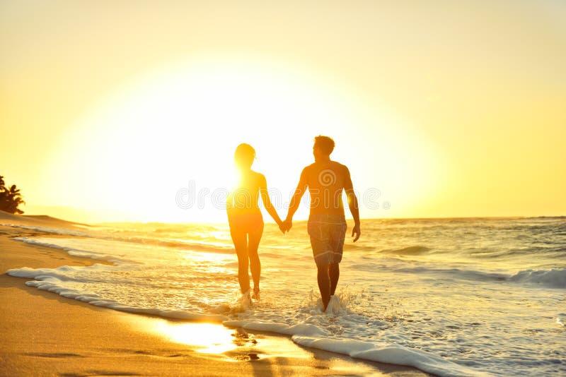 Romantiska bröllopsresapar som är förälskade på strandsolnedgången royaltyfria bilder